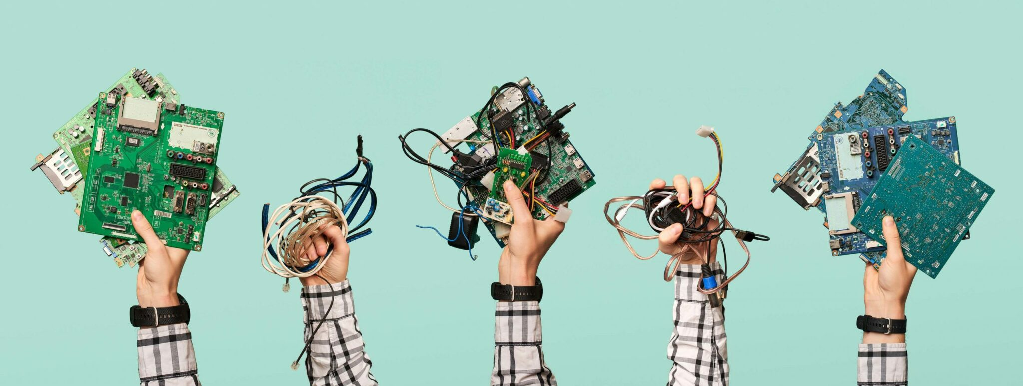 Hands holding electronic cords and circuit boards
